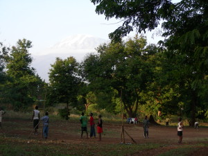 Soccer in Africa.  No grass, no nets, tattered ball, some have shoes.  Still fun!